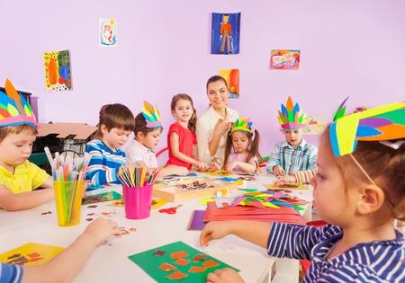 niños sentados: Grupo de los muchachos de los niños y niñas con el maestro haciendo manualidades con papel y cola sentado en la mesa en clase