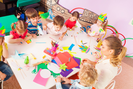 sit around: Group of kids sit around table and work with paper cardboard and draw pictures view from above Stock Photo