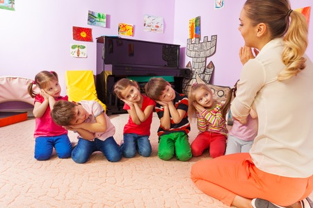 Group of kids in kindergarten playing sleep holding hands near head like teacher shows