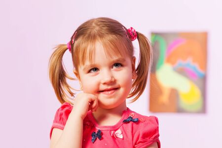 cheeky: Dreaming portrait of a girls with ponytails over the wall with picture Stock Photo