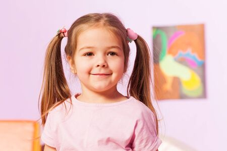 child smile: Girl with ponytails smile and pose over the wall with picture