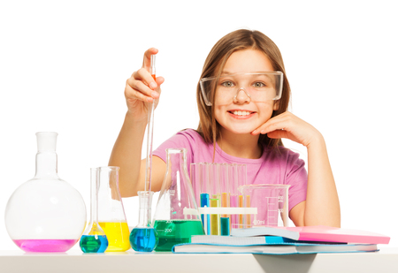 Young girl gathering with a pipette some blue reactant from the flask at the  laboratory Stock Photo