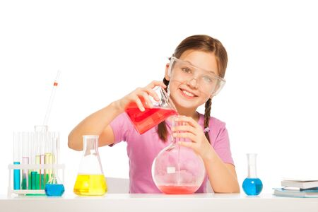 volumetric flask: One Caucasian schoolgirl pouring red liquid reactant from volumetric glass to the big flask