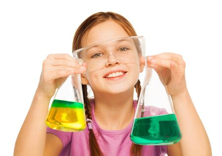 blinkers: One smiling Caucasian schoolgirl with two flasks filled with liquid reactant in safe eyewear