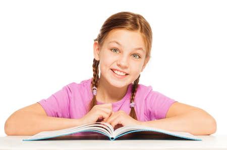 colegiala: Una colegiala sonriente estudiando sus lecciones en el escritorio aislado en blanco Foto de archivo