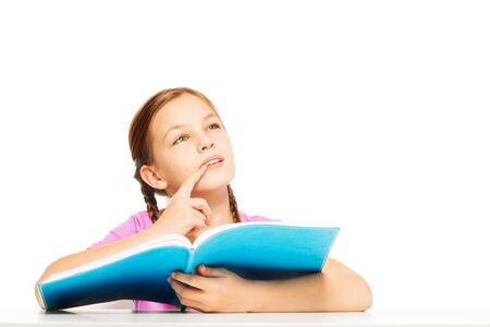 colegiala: Una colegiala pensativa sosteniendo su libro de texto con la tapa azul en su mano aislado en blanco