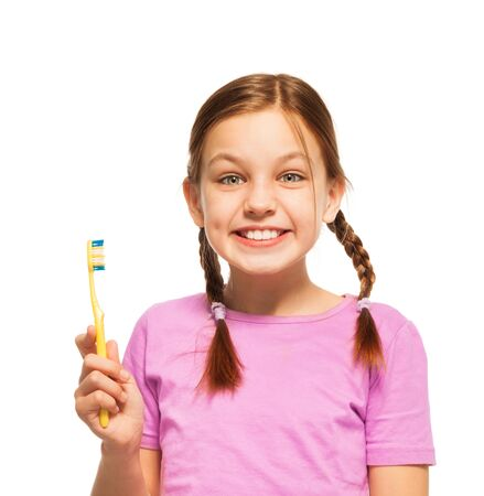 dientes sanos: niña sonriente feliz con los dientes sanos que sostienen el cepillo de dientes de color amarillo en la mano aislados en blanco