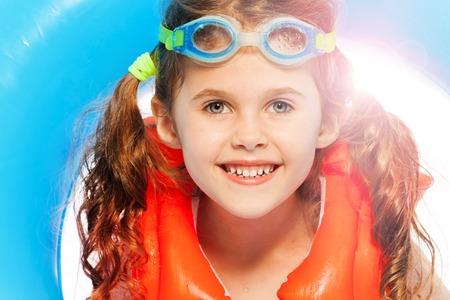 Das Porträt von niedlichen kleinen Mädchen im Schwimmen Brillen und orange Schwimmweste ihren blauen Gummiring hält