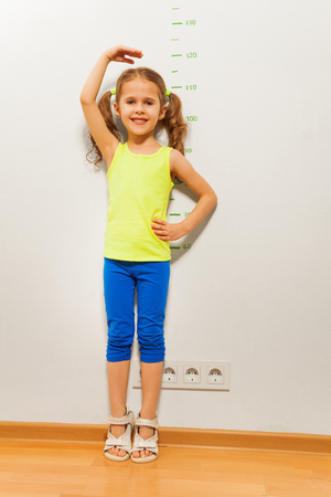 Little girl standing by the wall with drawn scale at home and show her height on the wall Stock Photo