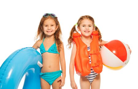Two little girls in swimsuits with blue rubber ring and colored wind-ball isolated on white