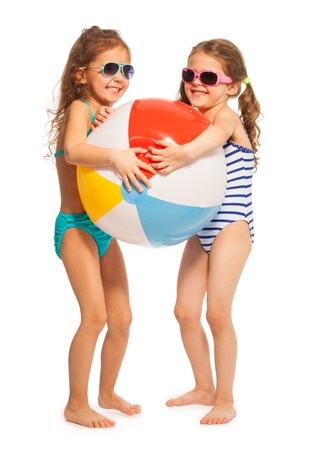 small girl: Two little swimmers in sunglasses catching together big colored wind-ball isolated on white