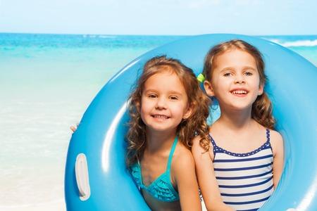 traje de baño: Dos muchachas divertidas en trajes de baño mirando a cabo el gran anillo de goma azul en la orilla del mar en verano