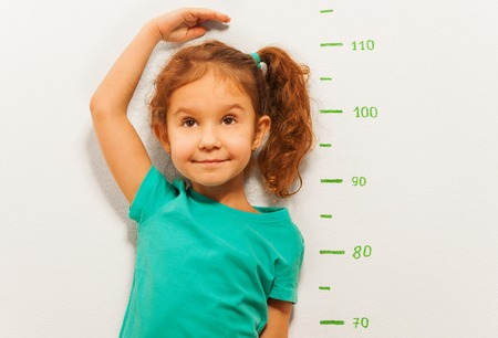 Close portrait of little girl standing by the scale drawn on the wall in living room and measure her height with hand Фото со стока