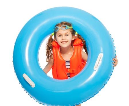 natacion niños: niña feliz en chaleco salvavidas de color naranja y gafas con gran anillo de goma azul