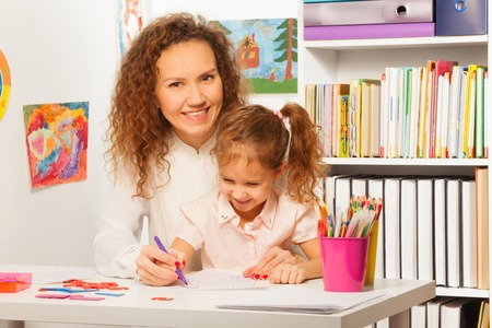 write: Teacher helps her pupil to write in a copybook at a school desk Stock Photo