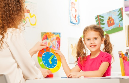 teaching: Smiling schoolgirl studying time with the cardboard clock model holding it in her hand Stock Photo