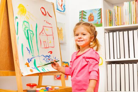 cute girl: Cute girl is drawing house, sun and plants using green brush at easel
