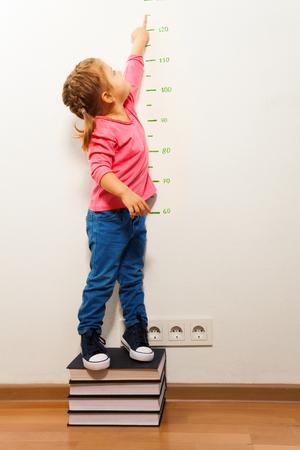 Ragazza divertente che misura la sua altezza di supporto a quattro grandi libri indicando il righello con il dito