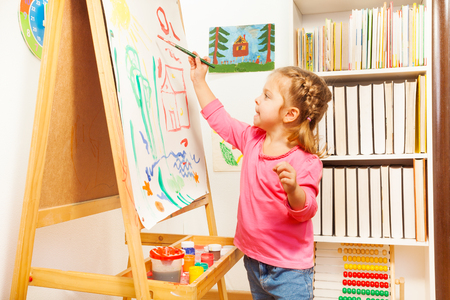 creative artist: Cute happy little girl, adorable preschooler, painting with  gouache on canvas standing on a wooden easel in a sunny white room at home or elementary school, creative young artist at work Stock Photo