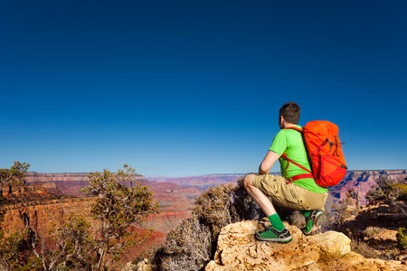 arm: Young man sit on squads on Grand canyon edge view from behind