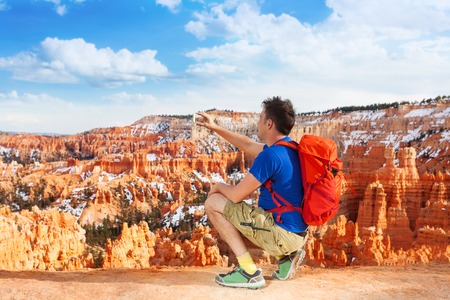 chicas guapas: Nice young man sitting on squads and take picture of Bryce canyon with smartphone