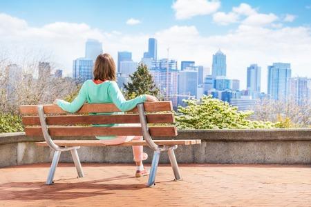 verano: Joven mujer sentada en el banco y mirando a Panorama de Seattle en el centro con muchos rascacielos