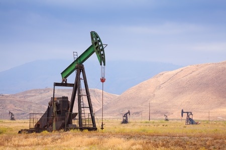 dug well: Several oil pumps and rigs operating on the back of beautiful mountains