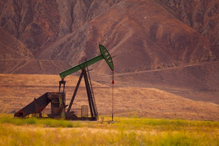 dug well: A producing oil well at the bottom of Californian mountain Stock Photo