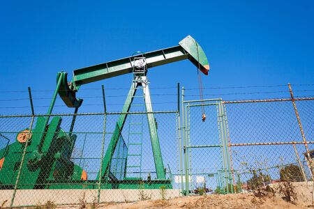chink: Green out of order oil-derrick surrounded by the chain-link fence against the blue sky