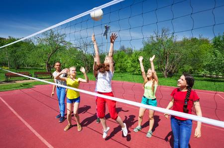 Volleybal spel onder tieners die spelen met de bal op de speelplaats in de zomer zonnige dag Stockfoto