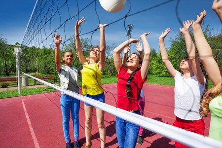 actively: Teens playing actively near the volleyball net on the court during sunny summer day outside
