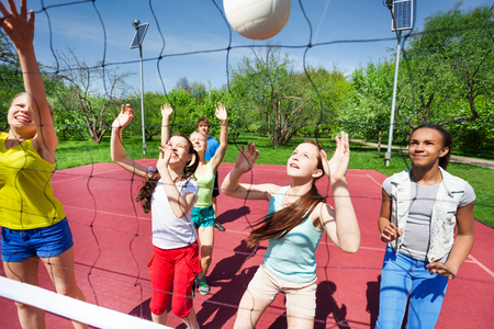 volleyball team: Teenagers in team play volleyball on the court during sunny summer day outside