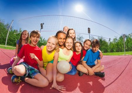 muchas personas: adolescentes divertidos felices sentado en cancha de voleibol que sostienen la bola durante el día soleado de verano