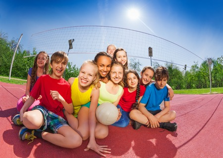 sports day: Happy funny teenagers sitting on volleyball court holding ball during summer sunny day