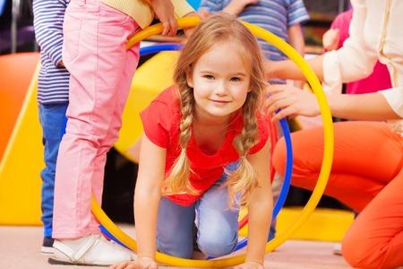 gymnastique: Belle fille de race blanche ramper si cerceaux jouer à un jeu à la maternelle