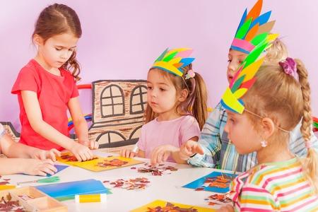 Girls and boy in kindergarten craft class gluing handmade postcard wearing cardboard headdress