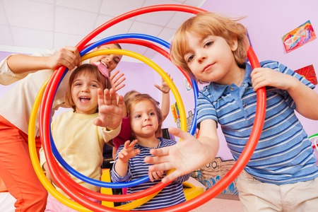 Group of little boys and girls with teacher pose smiling and happy with hoops