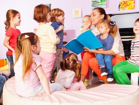 maestra preescolar: Profesor con los niños chicos y chicas leer y discutir el libro sentados juntos en la clase
