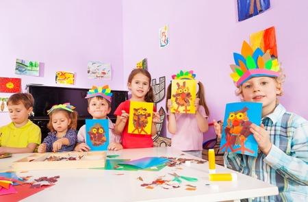 mignonne petite fille: Groupe de garçons et de filles enfants montrer leurs images d'artisanat par la table avec du carton et de la colle épiaison chapellerie main