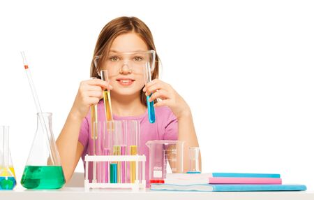 blinkers: One young Caucasian schoolgirl in safe eyewear studying chemistry at the desk in laboratory