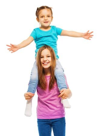 One little girl in turquoise t-shirt sitting on her elder sister's shoulders