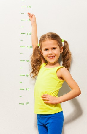 tall: Happy smiling little girl measure height with hand on the scale drawn on the wall