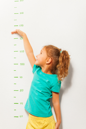 measure height: Little girl shows her height on a scale on the wall once she grow up