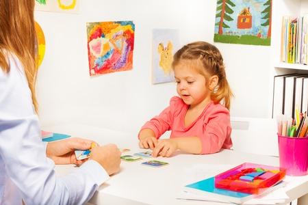 Dziewczynka biorąc kart ze stołu w trakcie posiedzenia w klasie na białym krześle