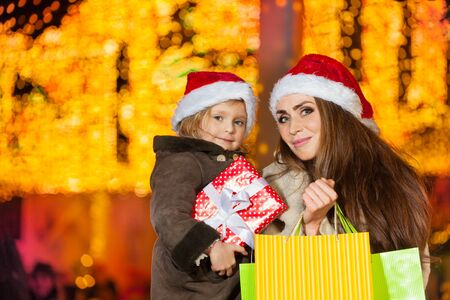 Smiling mother and her little daughter with holiday presents in their hands Stock Photo