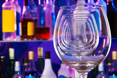 winy: Row of wine glasses close-up with bar and bottles on background Stock Photo