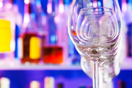 winy: Many glasses for wine standing in the row in bar with bottles standing on the shelf on back Stock Photo
