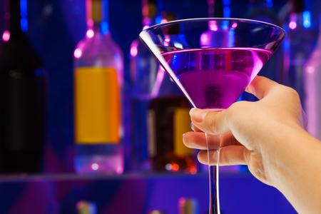 女性の手のクローズ アップ撮影は、バーでアルコール カクテルを飲むとマティーニのグラスを保持します。