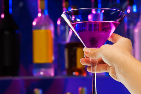 Close-up shoot of female hand hold martini glass with alcohol cocktail drink in the bar