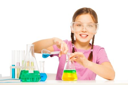 blinkers: Young Caucasian schoolgirl mixing blue and yellow reactants in flask at the laboratory isolated on white Stock Photo